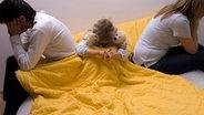 Trauriges Kind zwischen seinen streitenden Eltern  Foto: Picture Allicance