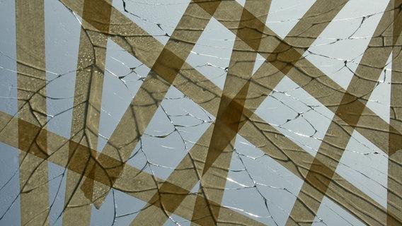 Eine kaputte Glasscheibe mit Rissen, die mit Klebeband abgeklebt sind. © Dot.ti / photocase.de Foto: Dot.ti / photocase.de