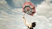 Eine Frau hält einen Regenschirm fest, der wegzufliegen droht. © Jonathan Schöps / photocase.de Foto: Jonathan Schöps / photocase.de