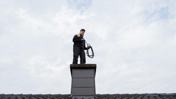 Ein Schornsteinfeger auf dem Dach. © picture alliance / dpa Foto: Rolf Vennenbernd