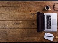 Ein Mann sitzt mit einem Laptop, Kalender und Smartphone an einem Tisch und arbeitet. © imago/Westend61 Fotograf: Westend61