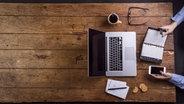 Ein Mann sitzt mit einem Laptop, Kalender und Smartphone an einem Tisch und arbeitet. © imago/Westend61 Foto: Westend61