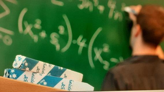 Ein Lehrer schreibt etwas an die grüne Tafel. Im Vordergrund Kreide. © fotolia