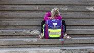 Ein trauriges Kind sitzt, auf seinen Schulranzen gelehnt, auf einer Treppe. © imago/Westend61