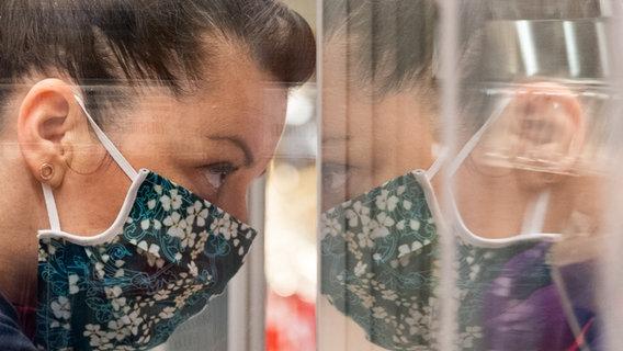Eine Frau trägt einen bunten Mundschutz und lehnt gegen ein Fenster. © picture alliance/Robert Michael/dpa-Zentralbild/dpa Foto: Robert Michael