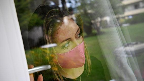 Eine Frau trägt einen Mundschutz und öffnet ein Fenster. © picture alliance / Sven Simon Foto: FrankHoermann/SVEN SIMON