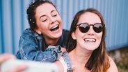 Zwei Freundinnen machen zusammen ein Selfie und lachen dabei. © photocase.de / criene Foto: photocase.de / criene