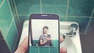 Eine Frau hält vor einem Waschbecken ein Smartphone, das ein Selfie zeigt. © Andeera / photocase.de Foto: Andeera / photocase.de