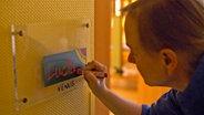 """Eine Frau schreibt den Namen """"Lucia"""" auf ein Schild. © NDR/Nikolas Müller Foto: Nikolas Müller"""