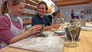 Männer und Frauen in einer Werkstatt beim Basteln. © NDR/Nikolas Müller Fotograf: Nikolas Müller