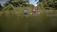 Zwei Personen auf einer Bank im Grünen. © NDR/Timo Grosspietsch Foto: Timo Grosspietsch