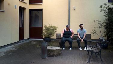 Zwei Menschen auf einer Bank in einem Innenhof. © NDR/Timo Grosspietsch Foto: Timo Grosspietsch