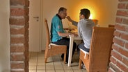 Ein Mann wird gefüttert. © NDR/Benjamin Arcioli Foto: Benjamin Arcioli