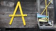 """Ein gelbes A mit der Aufschrift """"aufpassen"""" an einer Holzwand. © NDR/7 Tage Fotograf: Sebastian Gorski"""