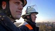 Hendrik Buth zusammen mit Feuerwehrmann Steven Eckardt auf der Drehleiter über Hamburg. © NDR/7 Tage Foto: Nikolas Müller