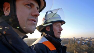 Hendrik Buth zusammen mit Feuerwehrmann Steven Eckardt auf der Drehleiter über Hamburg. © NDR/7 Tage Fotograf: Nikolas Müller
