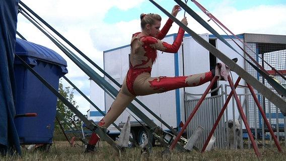 Eine Zirkusartistin macht Dehnübungen vor dem Zirkuszelt. © Lars Kaufmann Foto: Lars Kaufmann