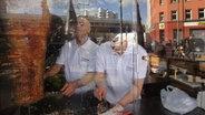 Zwei Männer hinter einer Glasscheibe in einer Dönerbude, schneiden Dönerfleisch.