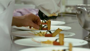 Auf einem Teller wird Essen drapiert. © NDR/Martin D'Costa Foto: Martin D'Costa