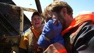 NDR-Reporter Lars Kaufmann beißt in einen rohen Fisch. Sein Fischerkamerade lacht.