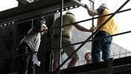 Drei Bauarbeiter auf einem Gerüst.