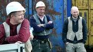 Bauarbeiter vor Containern.