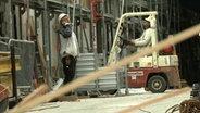 Bauleiter mit Gabelstaplerfahrer auf einer Baustelle.