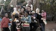 Drei deutsche Freiwillige in einem Waisenhaus in Afrika umringt von den Kindern dort.