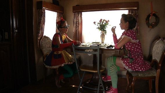Zwei Zirkusmädchen sitzen im Wohnwagen im Kostüm und essen Süßigkeiten.