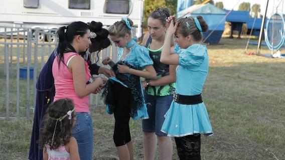 Mehrere Mädchen stehen um ein anderes Mädchen herum, deren Kleid gerissen ist, alle tragen ein Zirkuskostüm.