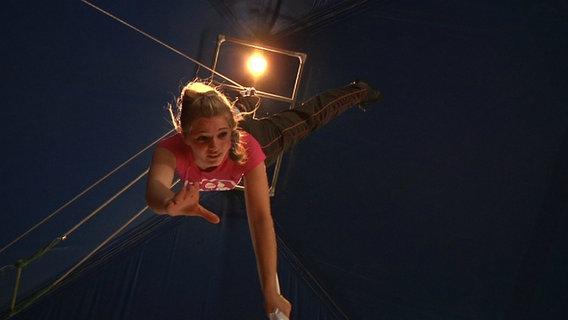Eine Zirkusartistin trainiert an einem Tuch hängend unter der Zirkuskuppel.