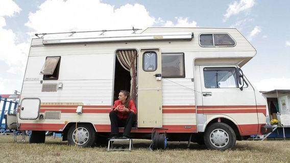 Ein Wohnmobil, vor dem eine Frau sitzt.