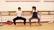 Zwei Ballerinas beim Training an der Stange.