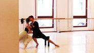Eine Ballerina und ein Balletttänzer, die sich küssen.