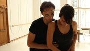Zwei Balletttänzer beim Proben im lichtdurchfluteten Tanzraum.