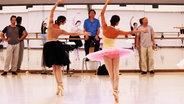 Zwei Ballerinas tanzen den Schwanensee bei einer Probe.