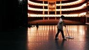 Blick von der Bühne in den Saal des Münchner Nationaltheaters. Eine Frau putzt die Bühne.