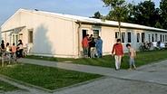 Asylbewerberheim mit Bewohnern davor.