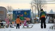Winterlandschaft: Zwei Kinder im Schnee, eins sitzt auf einem Schlitten und wird von einem Erwachsenen gezogen. © Sebastian Gorski Fotograf: Sebastian Gorski