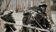 Ein Soldat in Tarnkleidung und -farbei bei einer Außenübung. © NDR/Willem Konrad Foto: Willem Konrad