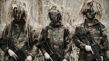Drei Bundeswehrsoldaten in Tarnkleidung bei einer Übung im Freien. © NDR/Willem Konrad Fotograf: Willem Konrad