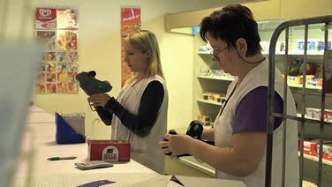 """Zwei Frauen """"schießen"""" Preisschilder an Waren. © NDR / Sebastian Bäumler Fotograf: Sebastian Bäumler"""
