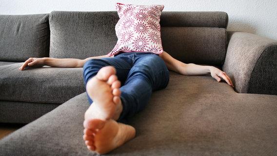 Eine Frau liegt, mit Kissen vor dem Gesicht, auf dem Sofa. © photocase.de / inkje Foto: photocase.de / inkje