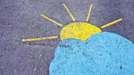 Eine auf Stein gemalte Sonne bahnt sich ihren Weg durch die Wolken. © samuelschalch / photocase.de Foto: samuelschalch