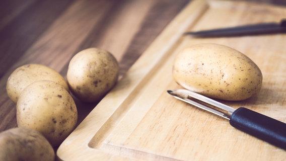 Ein Sparschäler, daneben Kartoffeln auf einem Brett. © Scampi_cfx / photocase.de Foto: Scampi_cfx / photocase.de
