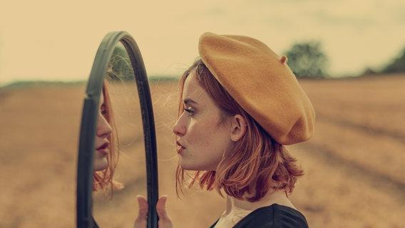 Eine Frau hält draußen einen runden Spiegel in den Händen und schaut hinein. © fmatte / photocase.de Foto: fmatte / photocase.de
