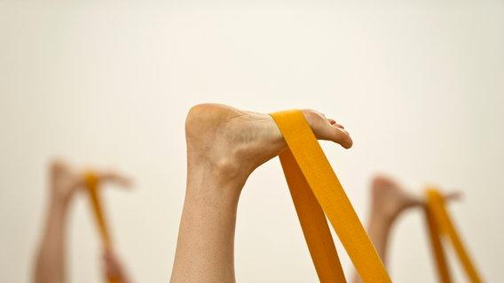 Zu sehen sind mehrere Füße, die mit Hilfe eines Bandes gedehnt werden. © schiffner / photocase.de Foto: schiffner / photocase.de