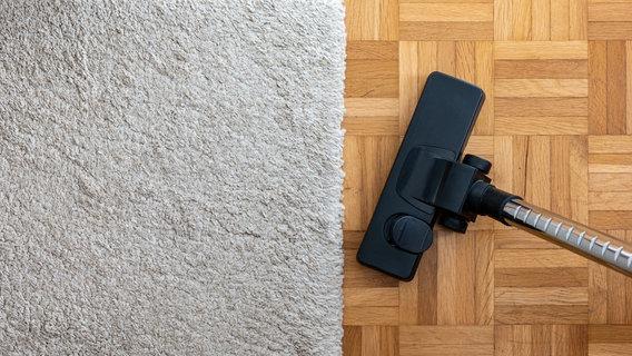 Heller Teppich und Staubsaugerbürste auf einem Holzfußboden. © Octavian Lazar / photocase.de Foto: Octavian Lazar / photocase.de
