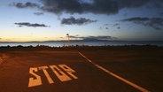 """Zu sehen ist ein Parkplatz am Meer. Auf dem Boden steht """"STOP"""". © imago/Westend61 Fotograf: Westend61"""