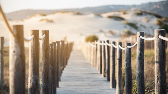 Ein Steg, der an einen Strand führt. © Davidpradoperucha / photocase.de Foto: Davidpradoperucha / photocase.de